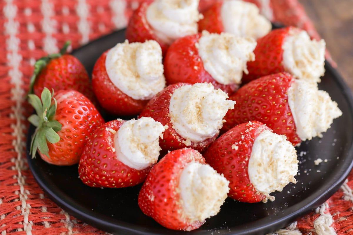 Cheesecake stuffed strawberries on a black plate