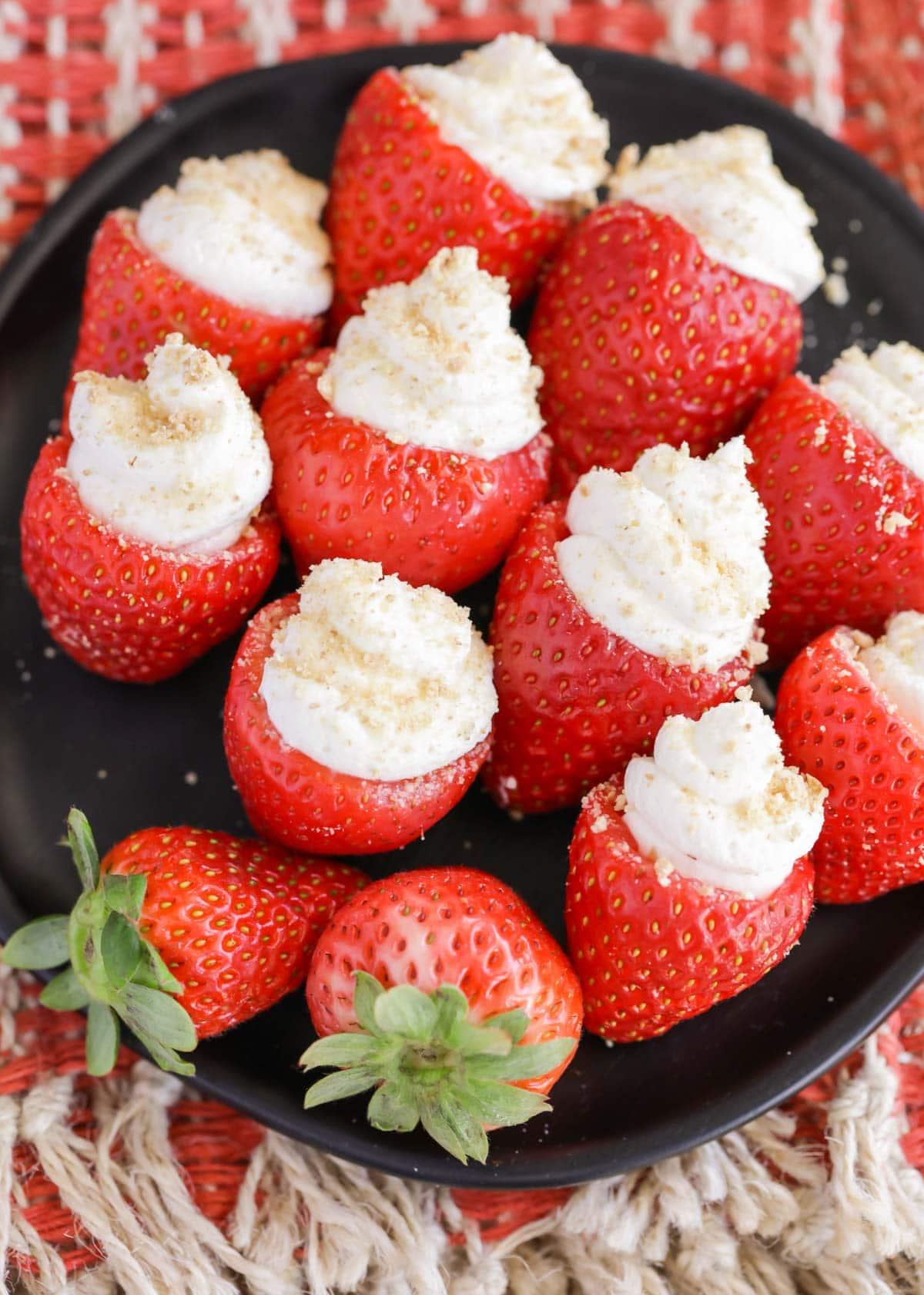 A plate full of cheesecake stuffed strawberries