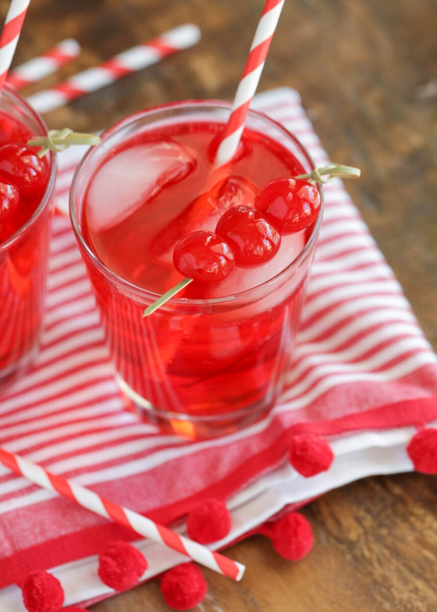 Shirley temple drink in a glass cup topped with cherries