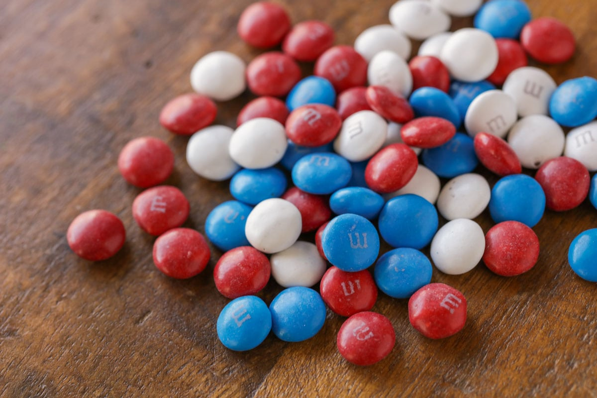 Red, white, and blue M&Ms poured on a wooden table.