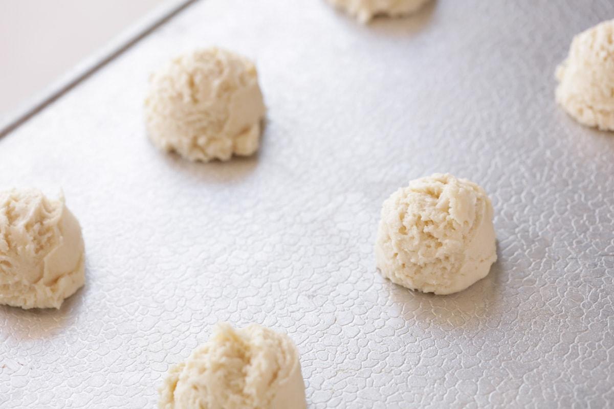 Double peppermint crunch cookie dough balls on a sheet pan