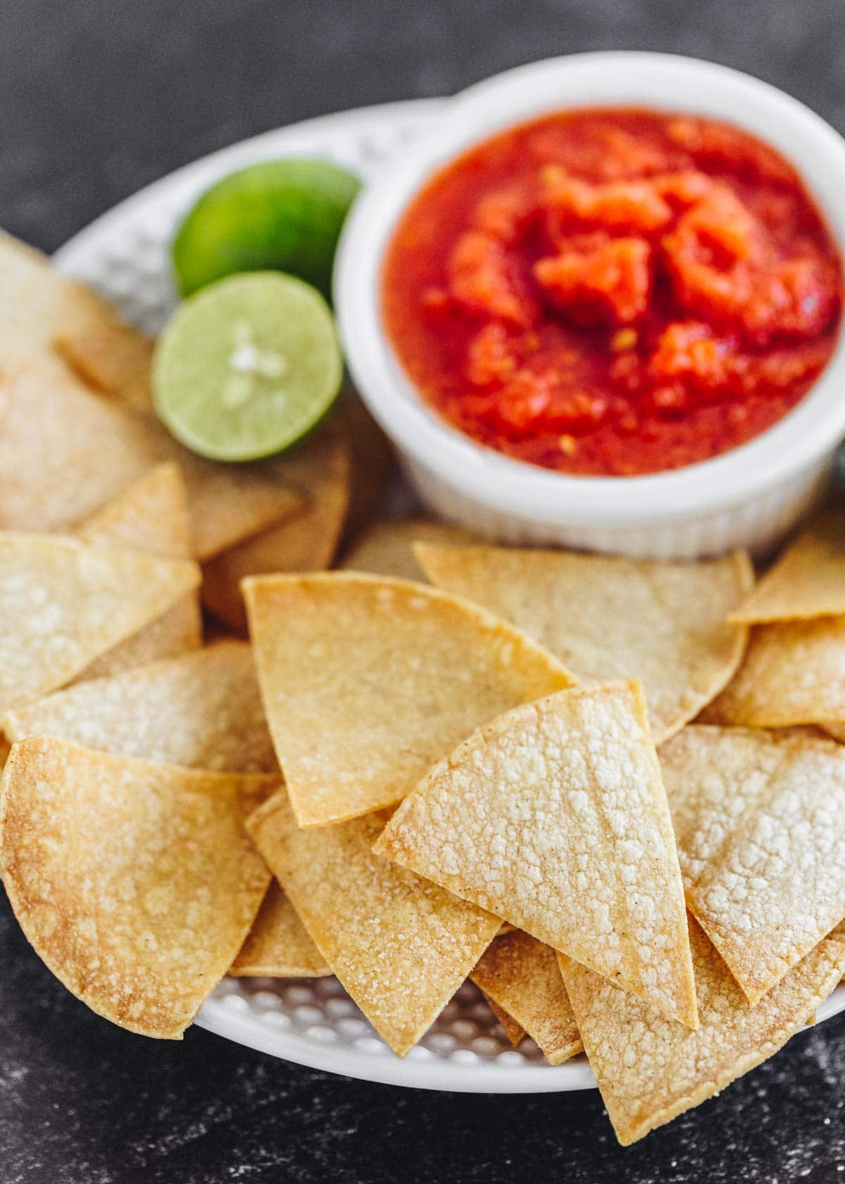 Oven baked tortilla chips on a plate with salsa