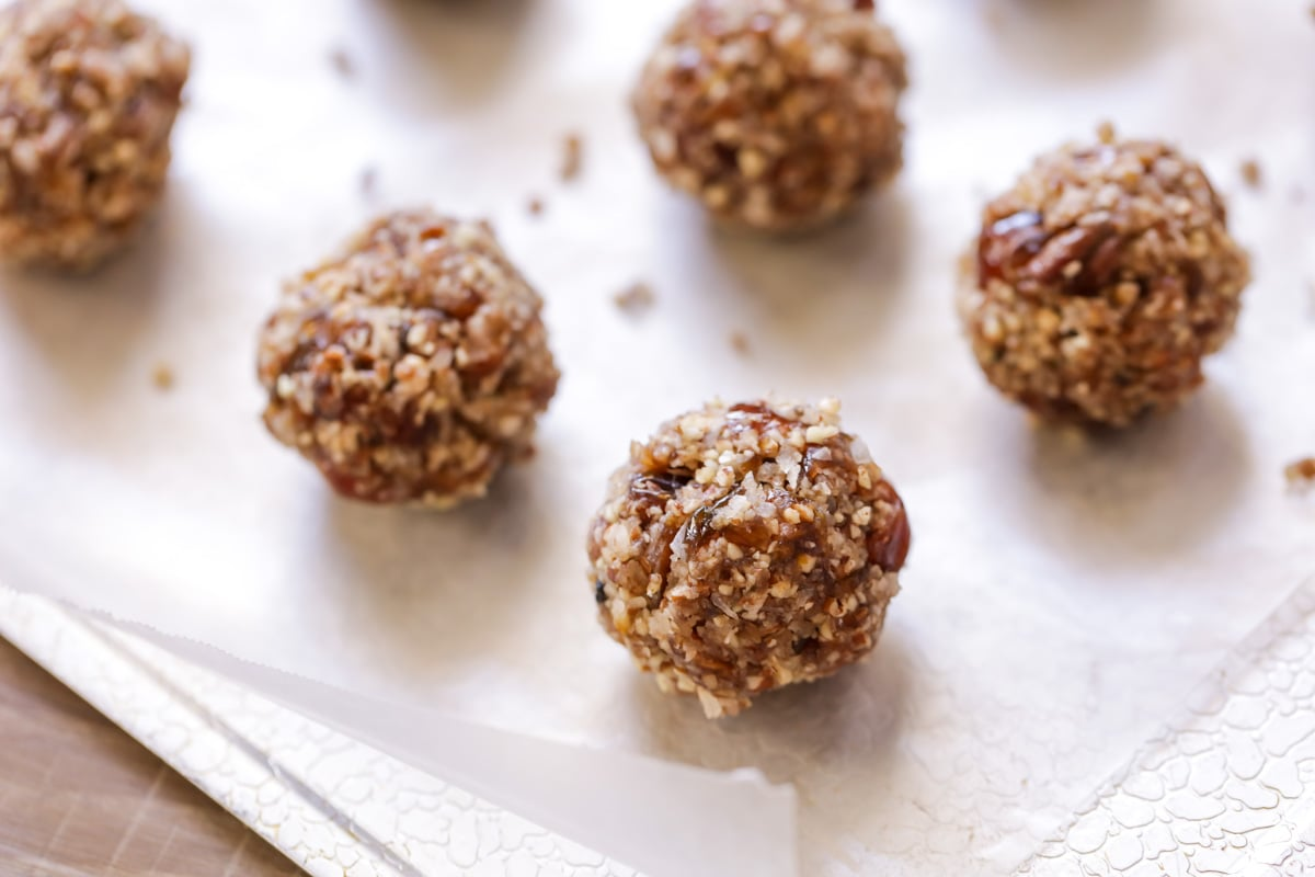Coconut date balls on a parchment paper lined baking sheet