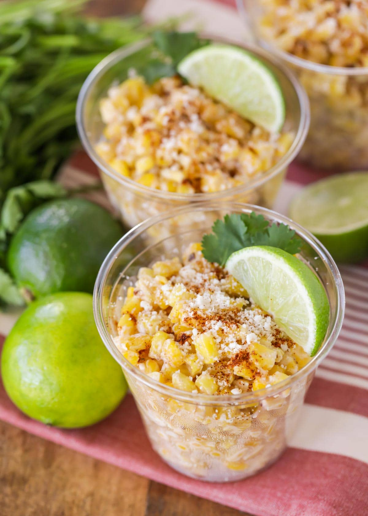 Corn esquites in a plastic cup with lime and cilantro