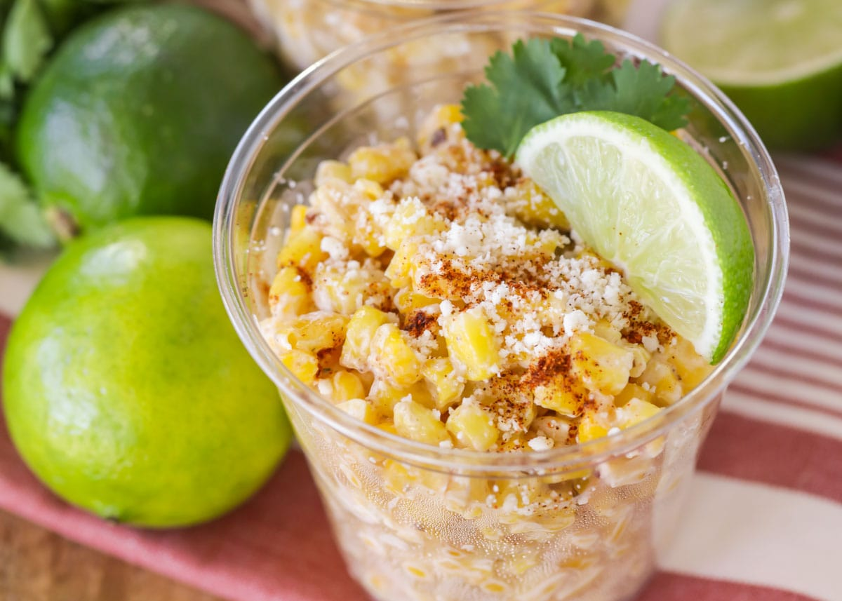 Esquites in a plastic cup with lime and cilantro
