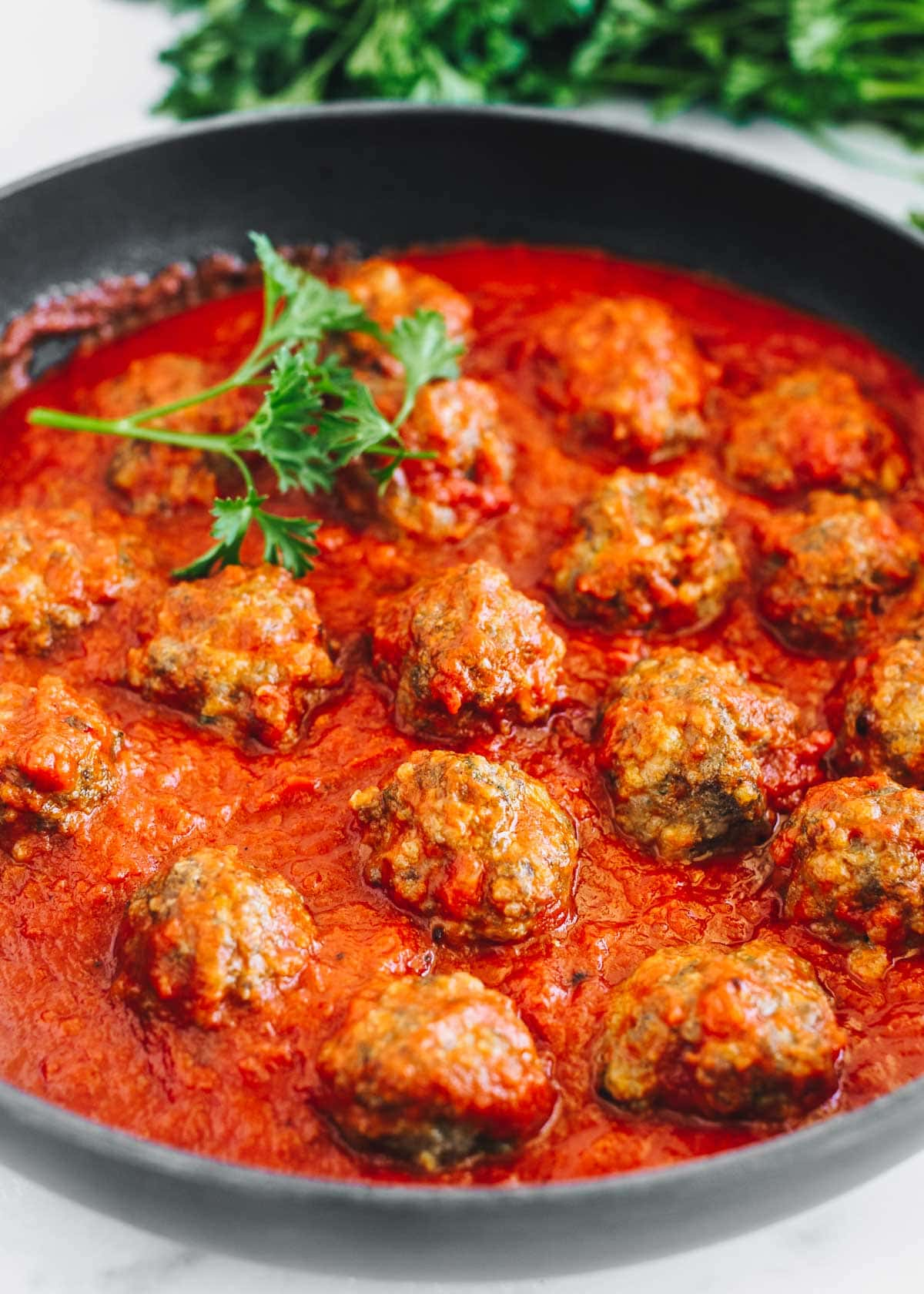 Best Italian meatballs in a skillet of marinara, garnished with parsley.