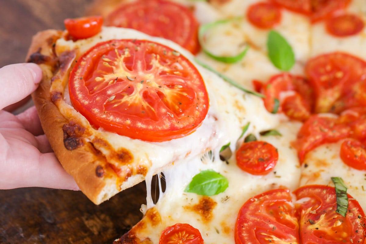 A hand grabbing a slice of tomato pizza