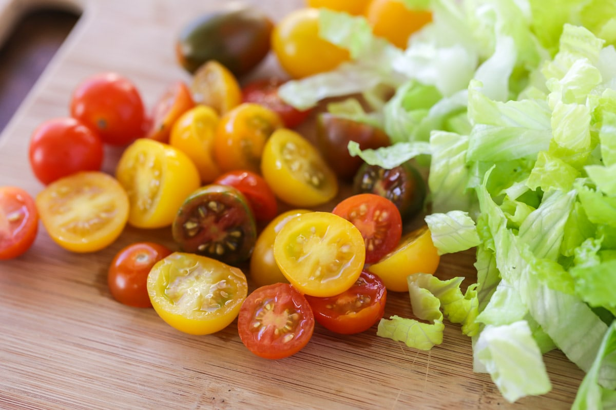 Sliced cherry tomatoes and shredded lettuce on a cutting board
