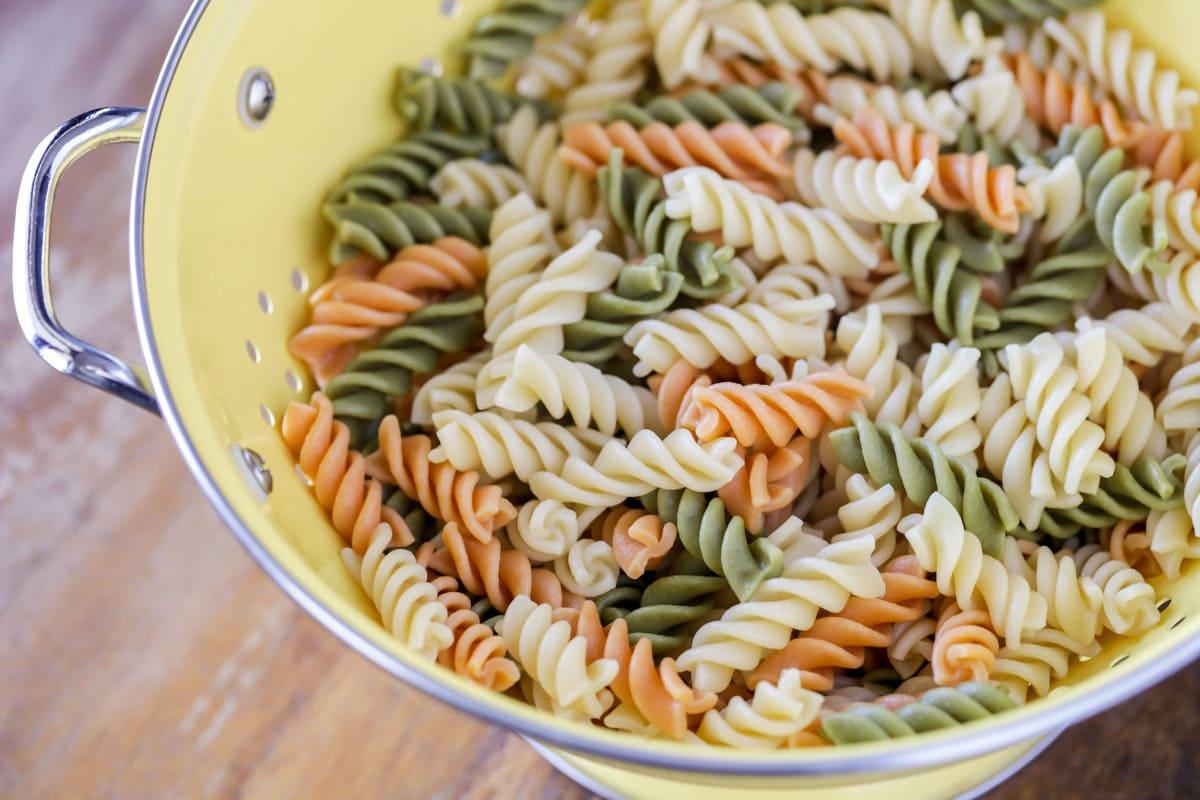 Tri-color pasta in a yellow colandar