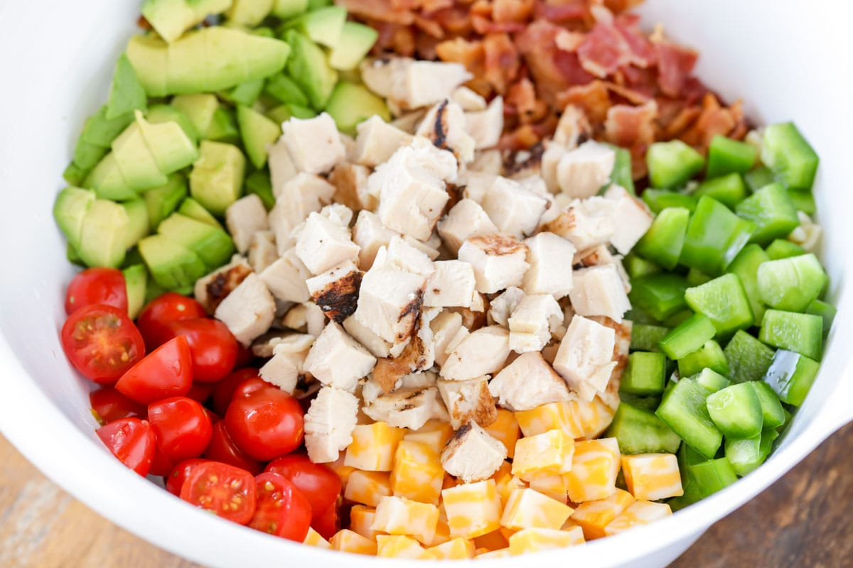 Diced tomato, chicken, avocado, bacon, cheese, and peppers in a white bowl