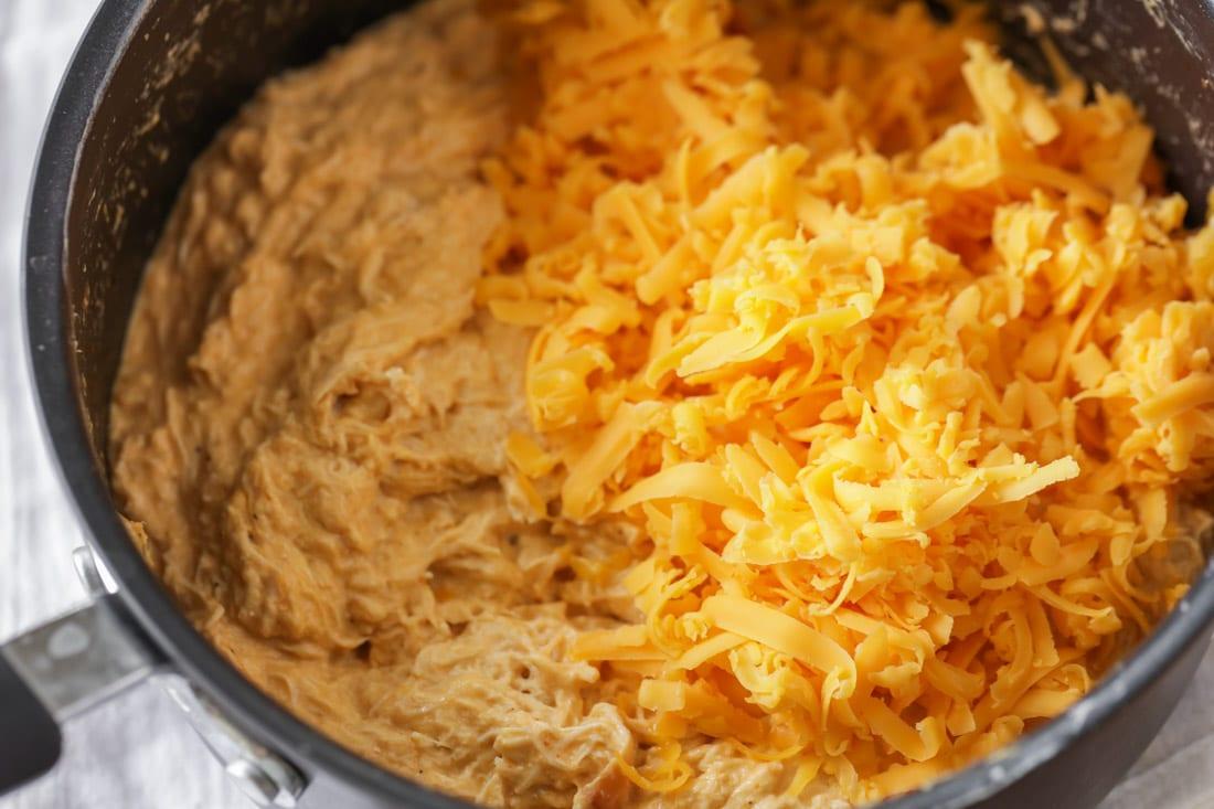 Mixing cheddar cheese into crockpot buffalo chicken dip