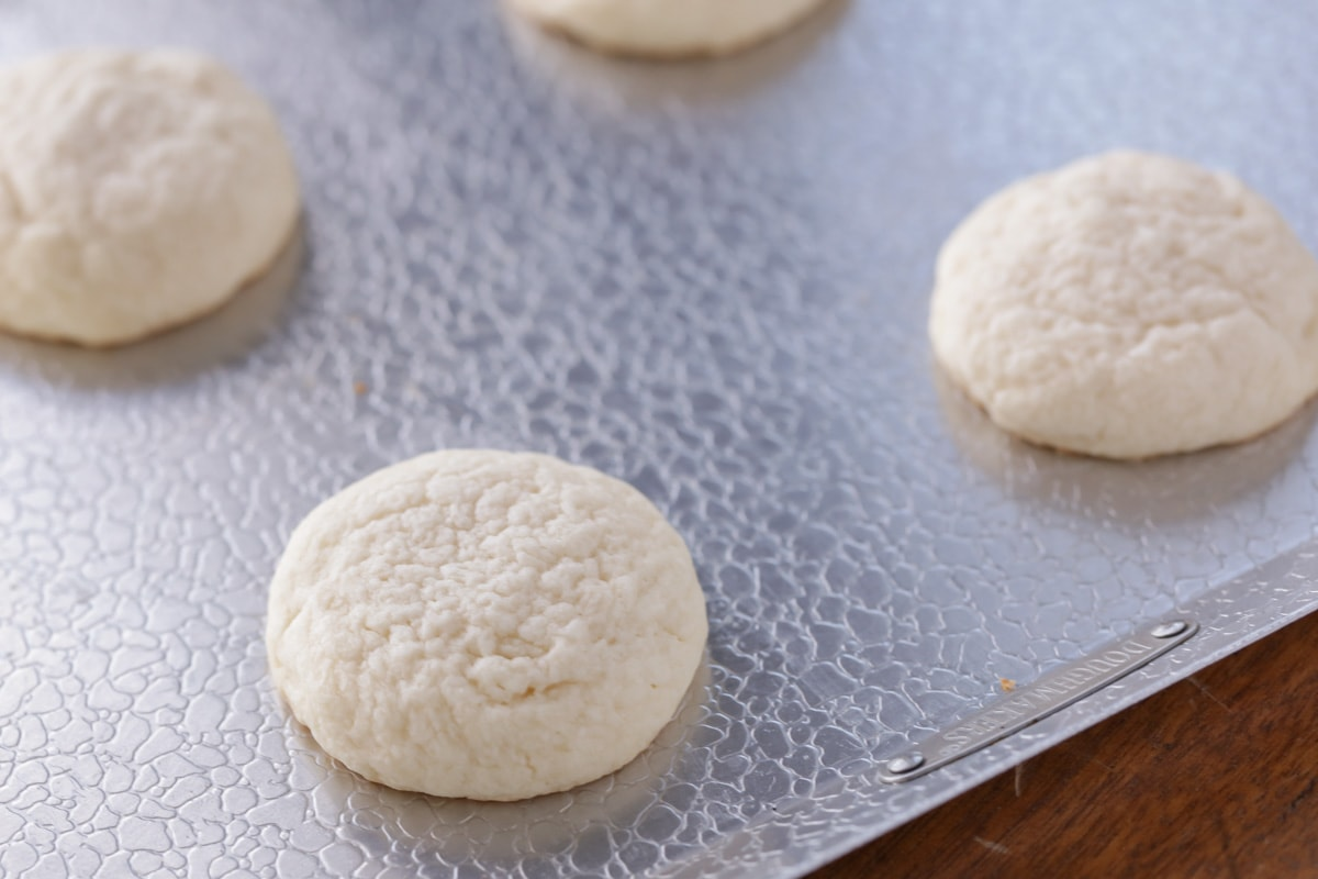 Cream cheese cookies baked and spaced on a cookie sheet
