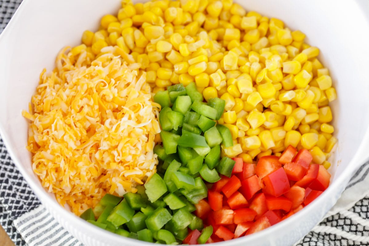 corn, cheese, and diced bell peppers in a white bowl