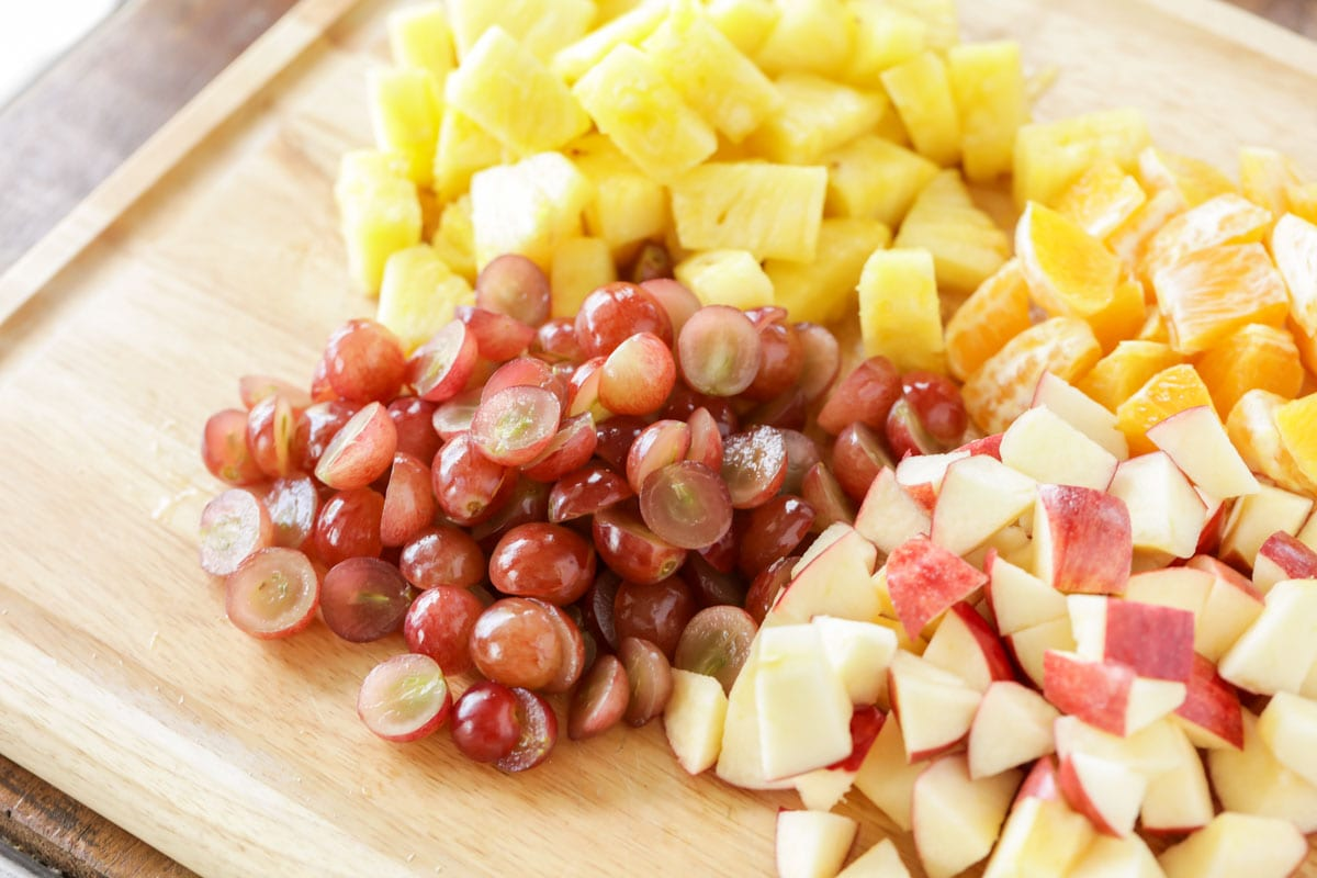 Ingredients for fall fruit salad recipe chopped on a cutting board
