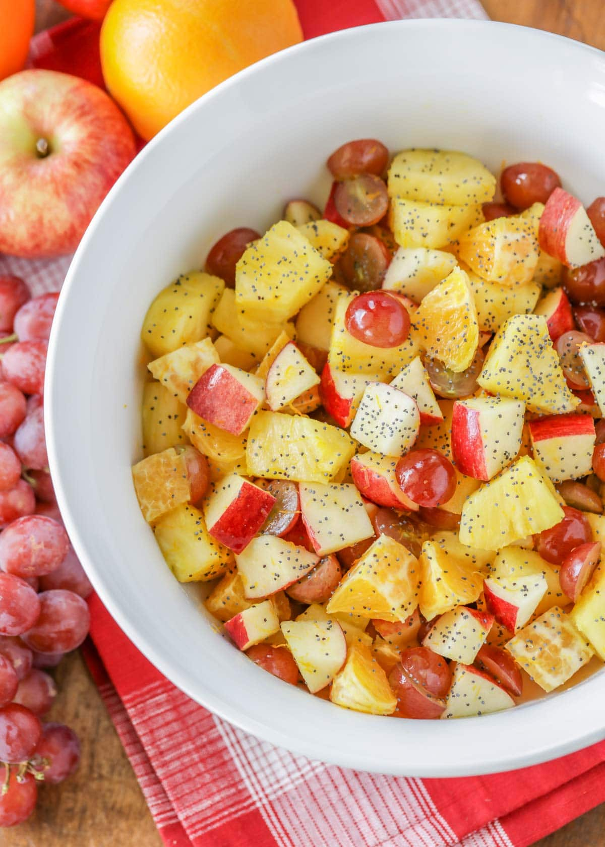 fall fruit salad dressed with poppy seed dressing in a white bowl