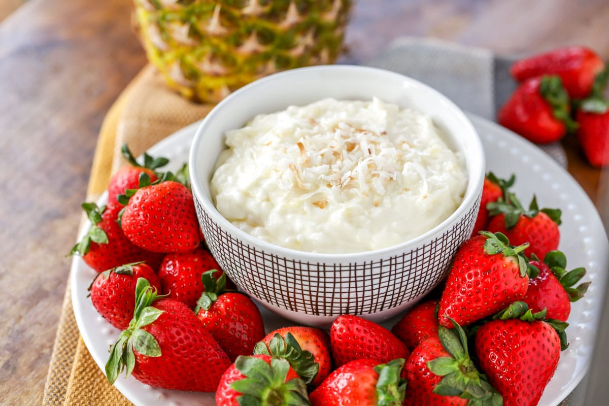 Pina colada fruit dip served in a white bowl surrounded by fresh strawberries