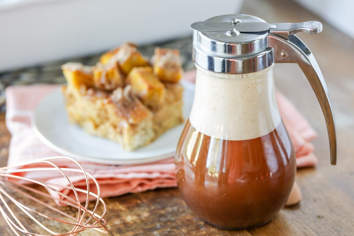 cinnamon buttermilk syrup in a syrup jar next to a plate of french toast bake.
