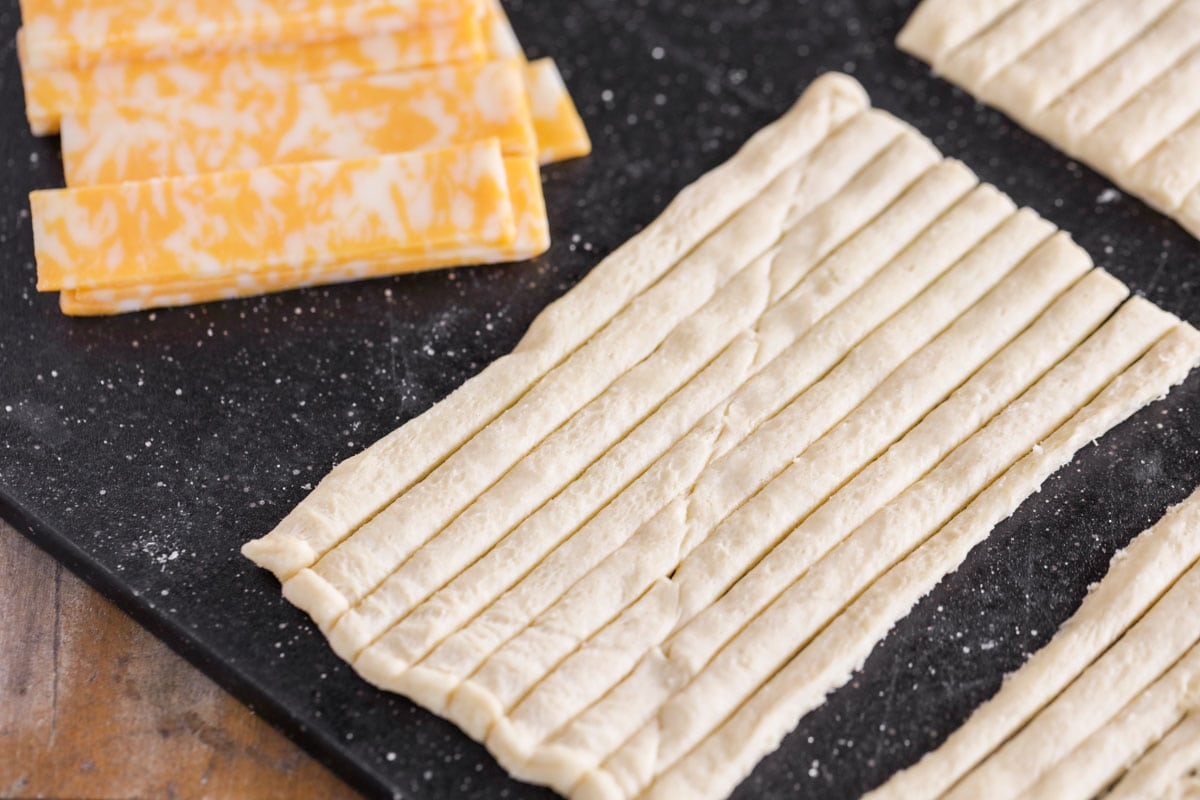 Cut crescent rolls and sliced cheese to use in mummy dogs recipe