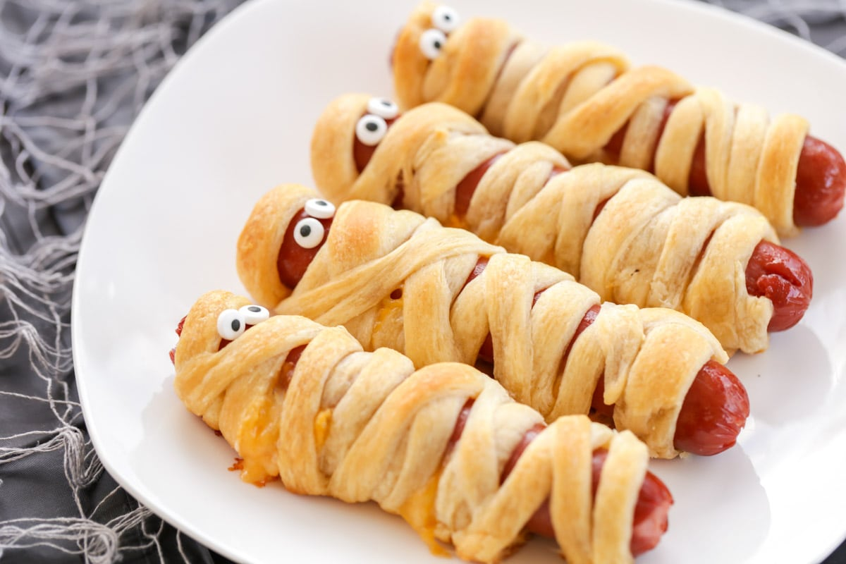 Mummy dogs with eyes on a white plate