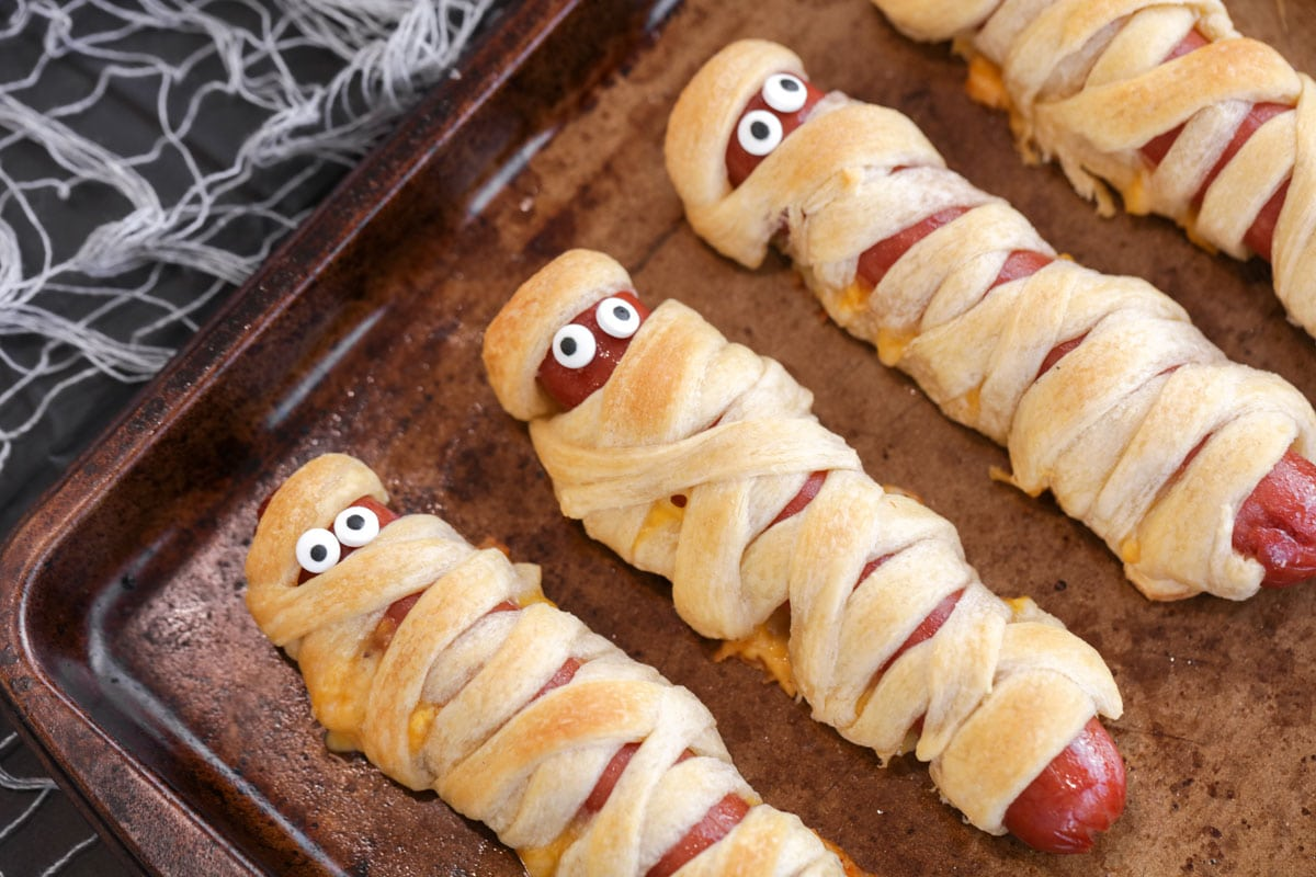 cooked mummy hot dogs with candy eyes on a pan