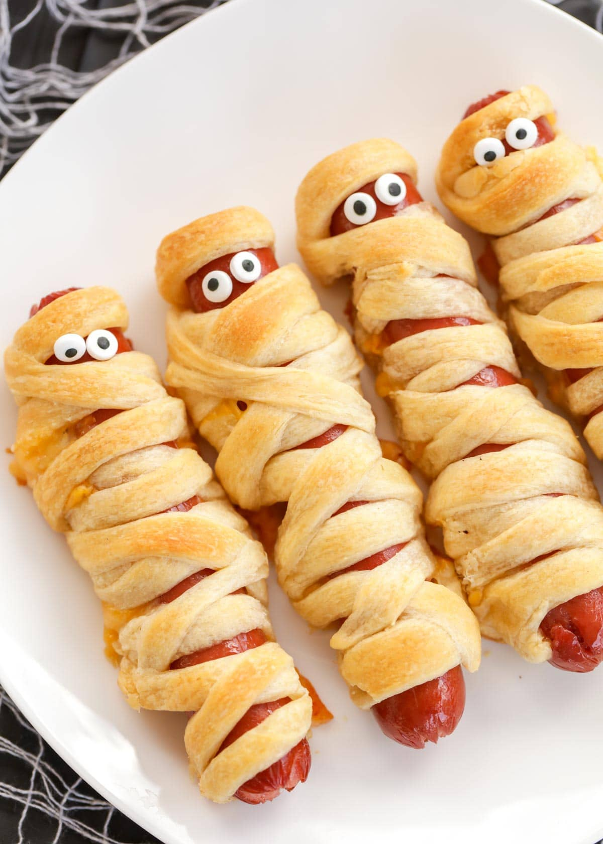 mummy dogs with candy eyes on a white plate