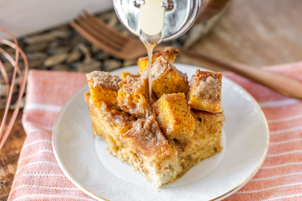 Pouring syrup on a plate of pumpkin french toast bake