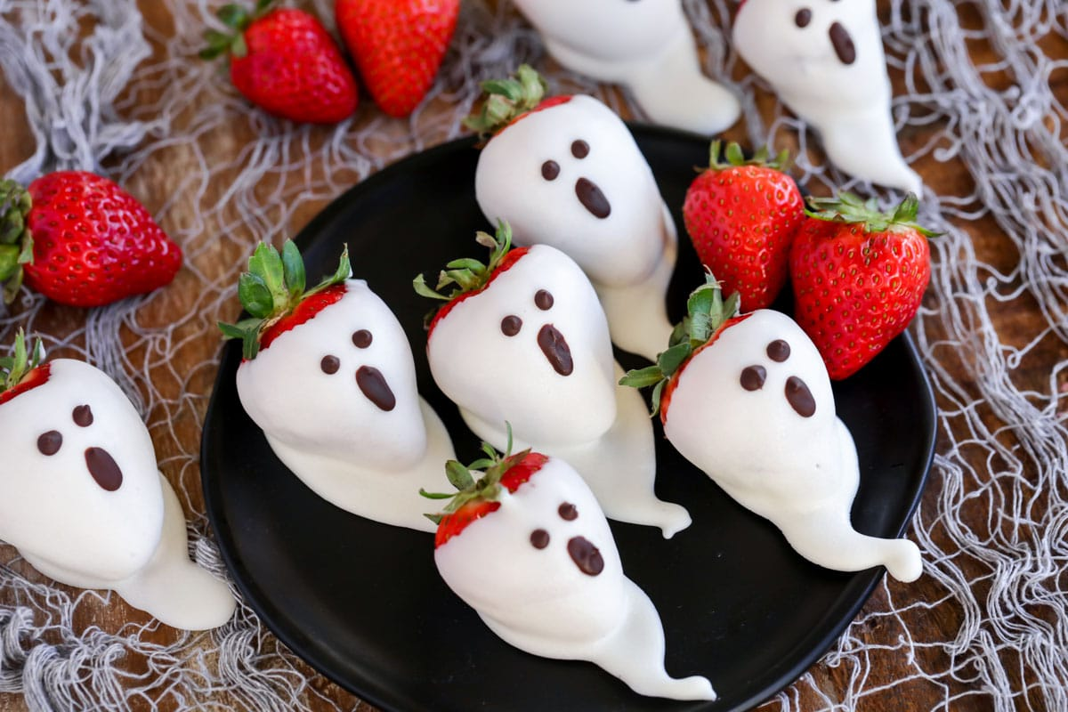 Dipped strawberry ghosts on a black plate