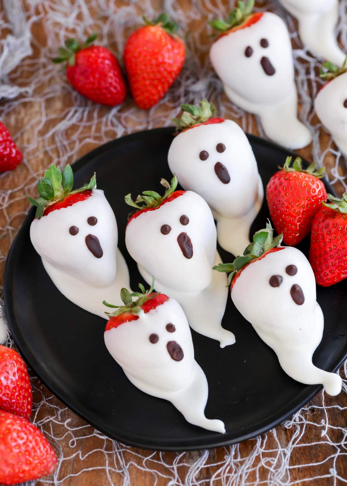 Strawberry ghosts on a black plate