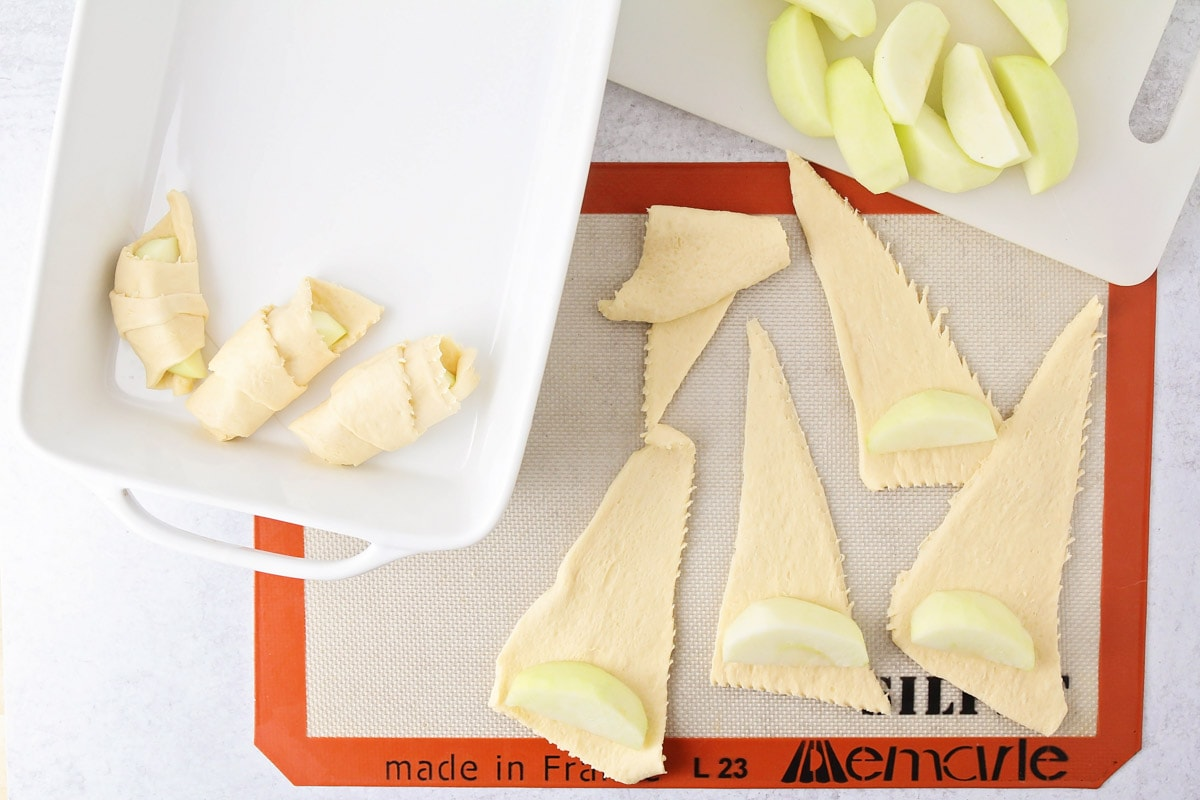 Rolling apple slices inside crescent roll dough