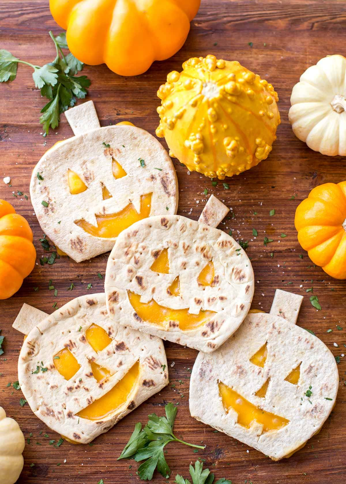 Pumpkin quesadillas shaped scattered next to gourds