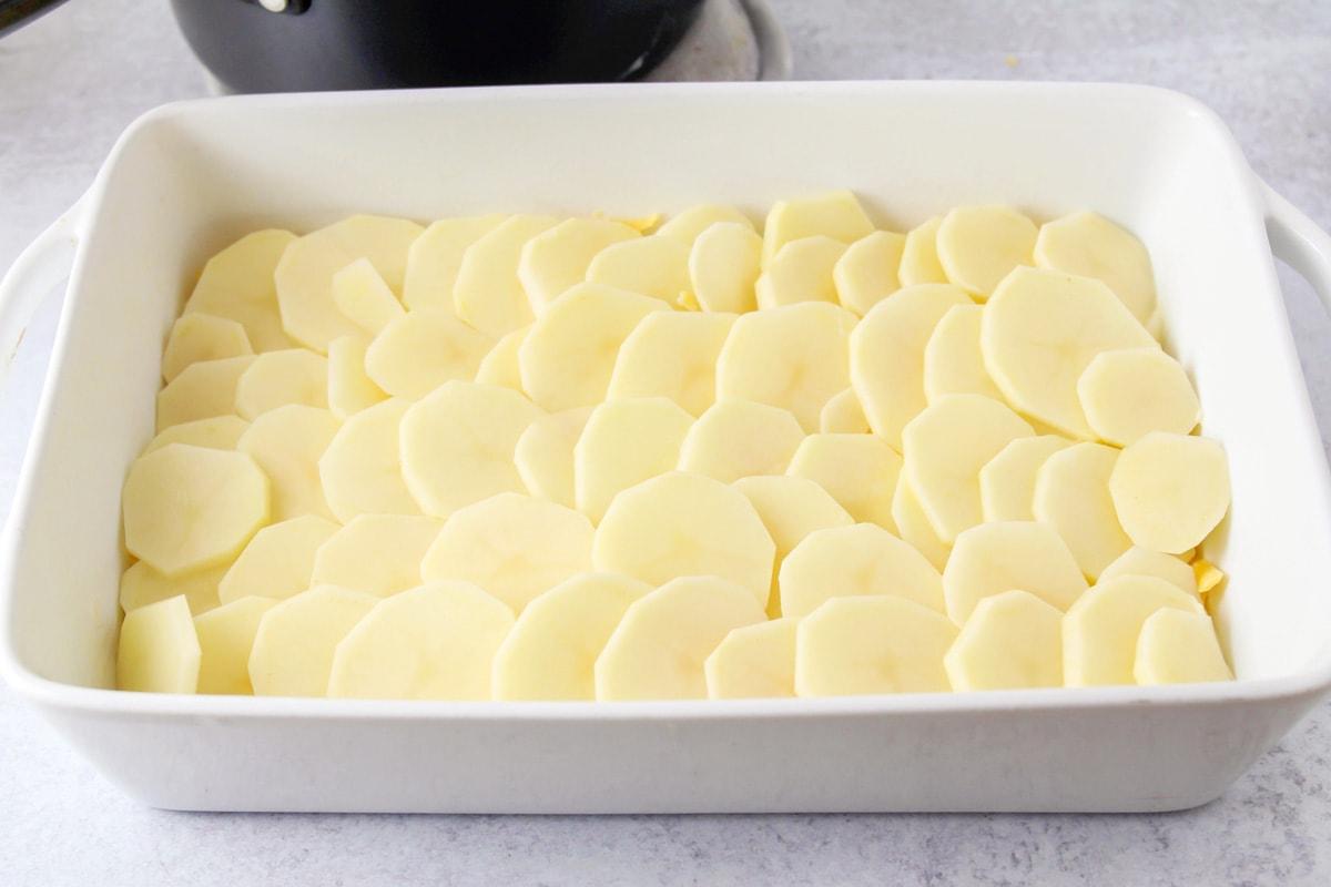 Layering cheesy scalloped potatoes in a white casserole dish