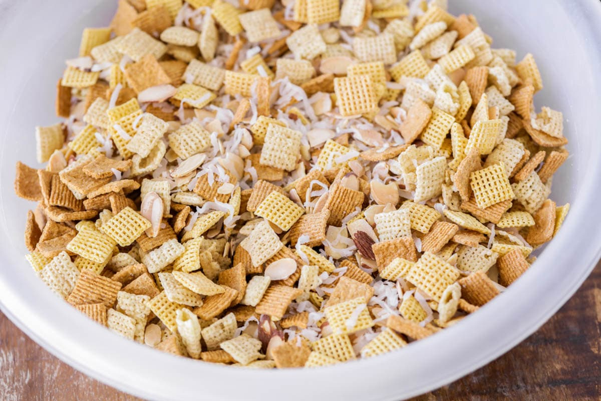 Chex, honey grahams, coconut and almonds in a white bowl