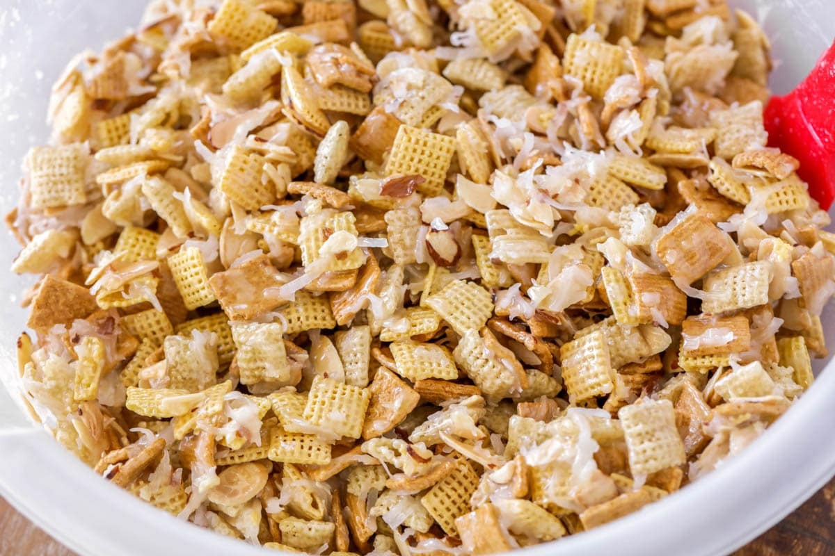 Homemade sweet chex mixed in a plastic bowl and covered in coconut