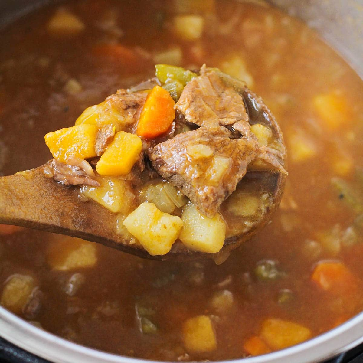 Scooping stew out of the instant pot with a wooden spoon