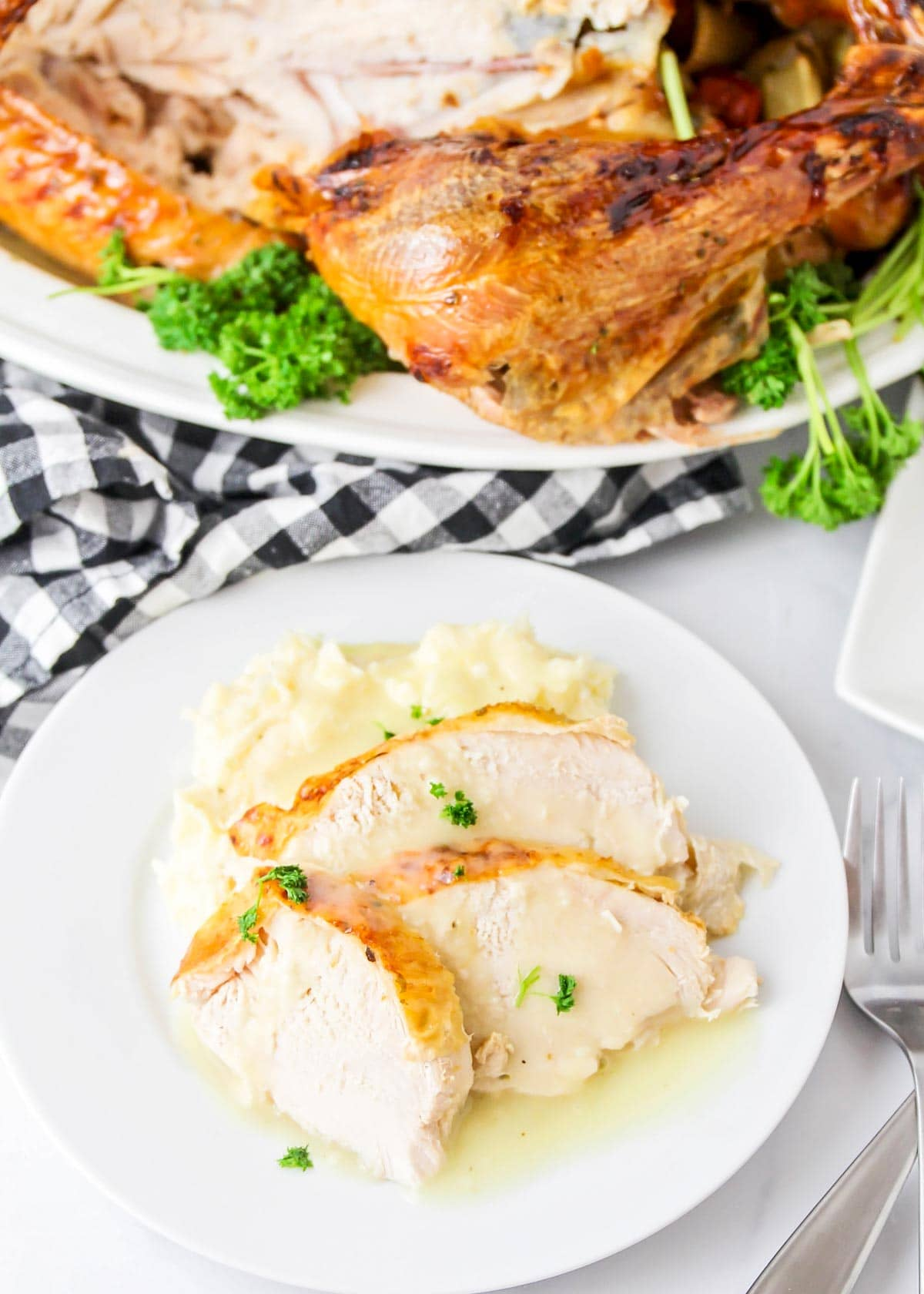 Sliced roasted turkey on a white plate served with mashed potatoes and gravy