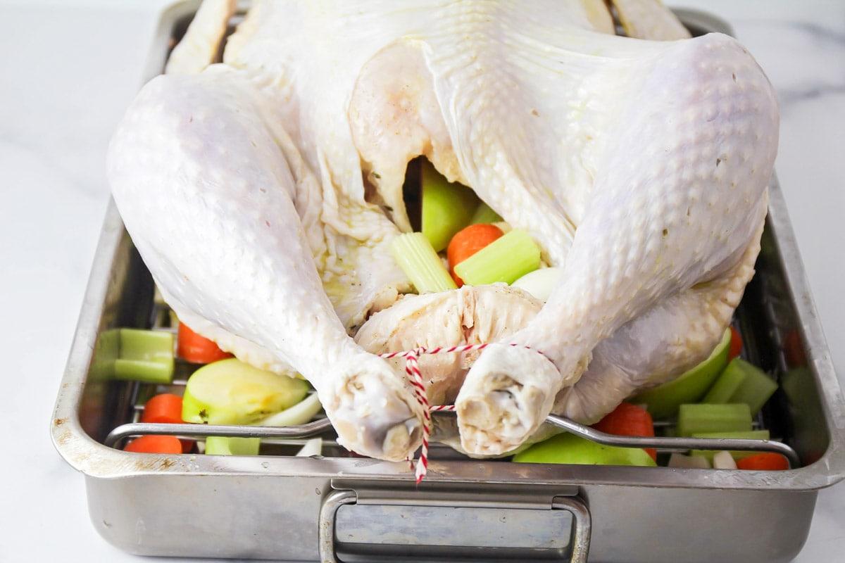 Turkey in a roasting pan on top of cut veggies