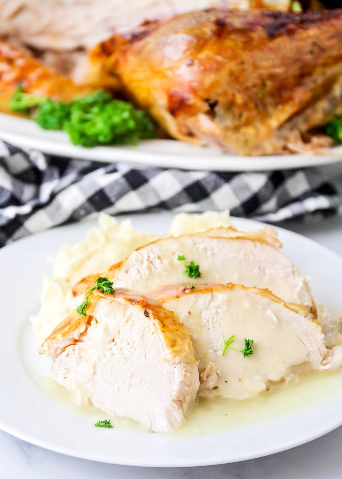 a plate of sliced turkey and mashed potatoes topped with turkey gravy.