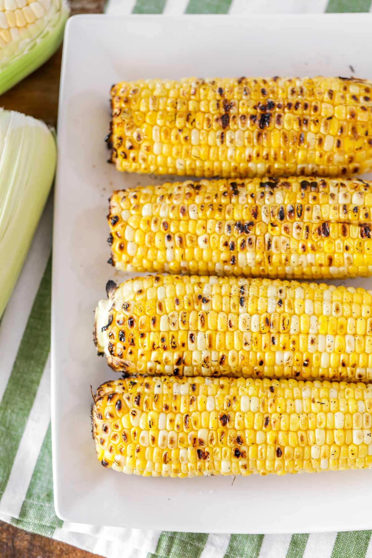 A white serving platter full of grilled corn